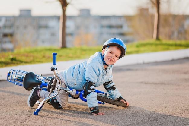 Uma criança pequena com capacete e proteção caiu de uma bicicleta no asfalto e não se feriu