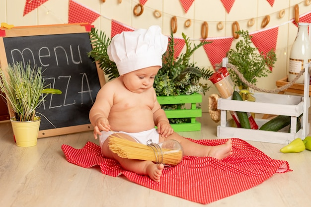 Uma criança pequena com chapéu de chef cozinha espaguete na cozinha
