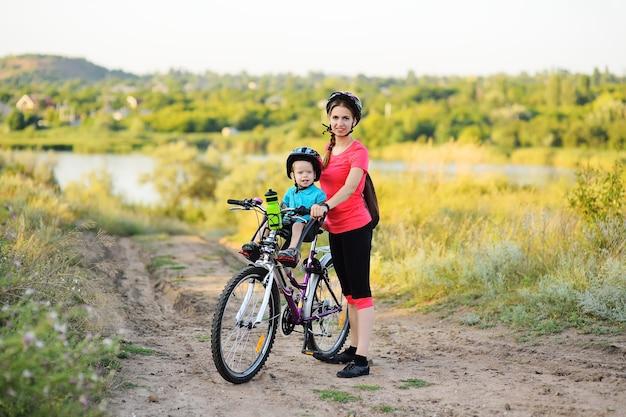 Uma criança pequena com um capacete protetor sorri sentada na cadeirinha de uma criança em uma grande mountain bike com sua mãe na superfície da grama verde e da natureza