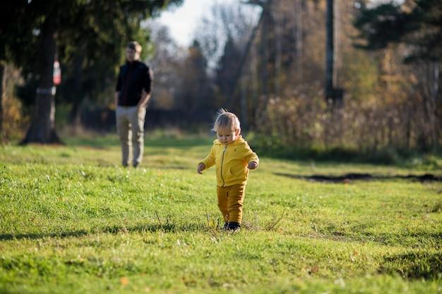 Uma criança pequena com uma jaqueta amarela fugiu de seu pai em um parque de outono, no verão indiano