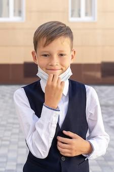 Uma criança pequena com uma máscara durante um surto do vírus perto do muro da escola