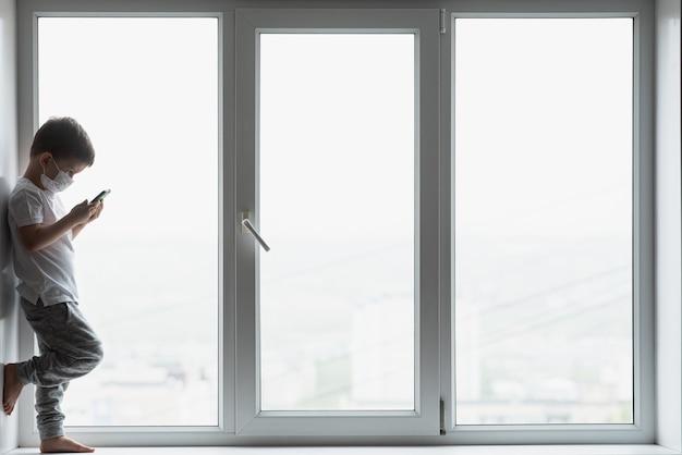 Uma criança pequena com uma máscara médica fica em quarentena em casa em uma janela com um telefone nas mãos.prevenção de coronavírus e covid - 19