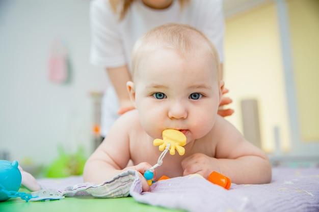 Uma criança pequena deitada de bruços recebe uma massagem em uma sala de massagem, ele tem um brinquedo na boca