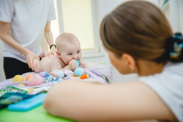 Uma criança pequena deitada de bruços recebe uma massagem em uma sala de massagens, sua mãe está ...