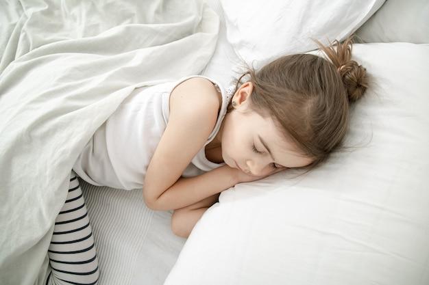 Uma criança pequena dorme com um pijama leve. conceito de saúde e sono durante o dia do bebê.