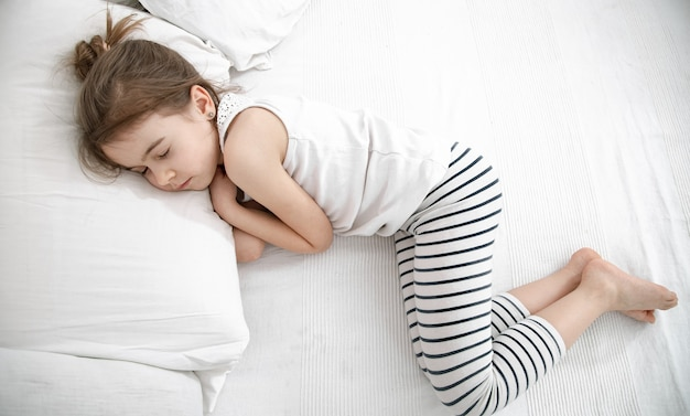 Uma criança pequena dorme com um pijama leve em uma cama leve. sono diurno do bebê e conceito de saúde.