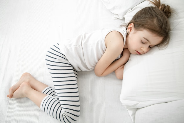 Uma criança pequena dorme com um pijama leve no contexto de uma cama clara. conceito de saúde e sono durante o dia do bebê.