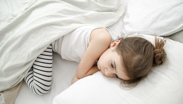 Uma criança pequena dorme na cama de pijama leve. conceito de saúde e sono durante o dia do bebê.