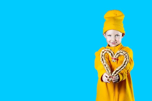 Uma criança pequena e bonita em uma jaqueta amarela e chapéu. segurando um coração trançado em fundo colorido brilhante.