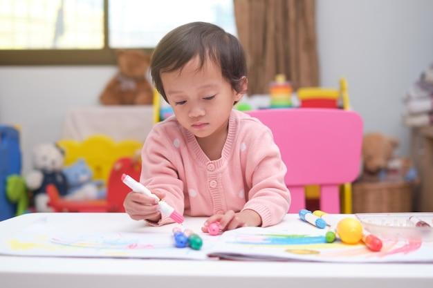 Uma criança pequena e fofa asiática pintando com giz de cera em casa