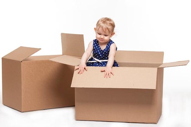 Uma criança pequena em caixas de papelão na superfície branca