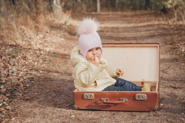Uma criança pequena em um terno quente se senta em uma mala na estrada. o conceito de mudança de residência, mudança, acessórios, ar fresco, falta de moradia, lar das crianças