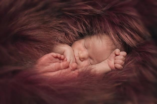 Uma criança pequena em uma pele vermelha encontra-se