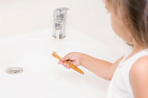 Uma criança pequena escova os dentes com uma escova de dentes de bambu.