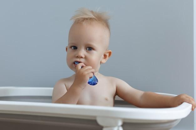 Uma criança pequena escova os dentes enquanto está sentada no banheiro
