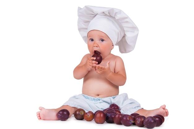 Uma criança pequena está comendo ameixas em um traje de chef em um branco.