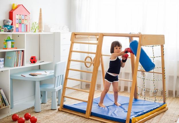 Uma criança pequena está envolvida em boxe em um complexo esportivo de madeira em casa.