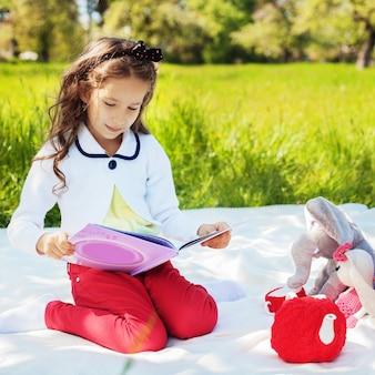 Uma criança pequena está lendo um livro interessante com contos de fadas.