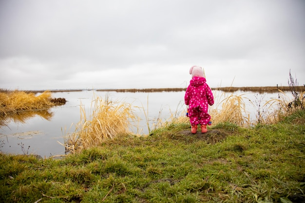Uma criança pequena fica na margem do lago e olha para a distância que caminha na natureza
