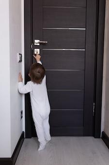 Uma criança pequena fica na porta e tenta sair da sala
