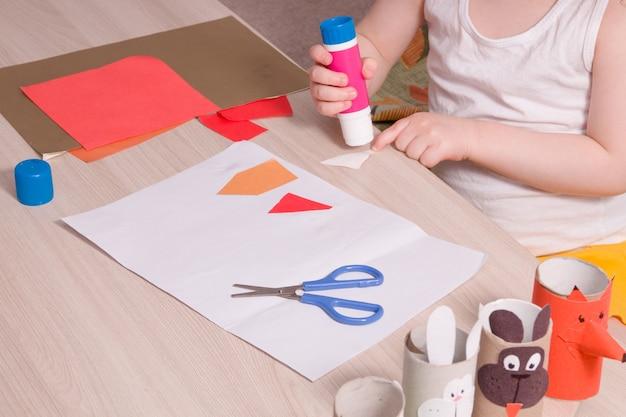 Uma criança pequena mancha o papel com cola
