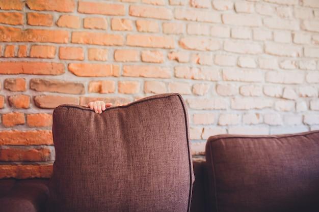 Uma criança pequena se escondeu atrás de um travesseiro no sofá.