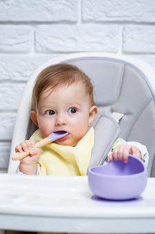 Uma criança pequena se senta em uma cadeira alta e come a comida em um prato com uma colher. utensílios de silicone para bebês para alimentar bebês