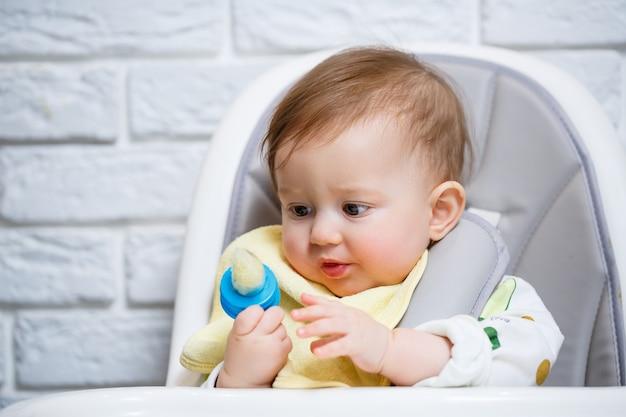 Uma criança pequena se senta em uma cadeira alta e come frutas através da rede. nibbler para alimentar bebês