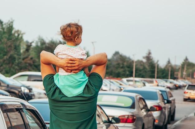 Uma criança pequena senta-se em seus ombros de pai