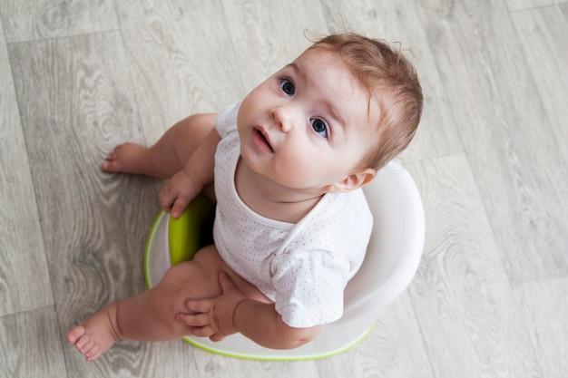 Uma criança pequena senta-se em um penico. vista de cima.