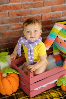 Uma criança pequena senta-se em uma caixa de madeira.