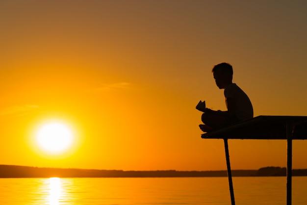 Uma criança pequena senta-se em uma ponte em uma pose dos lótus e prende um navio de papel no por do sol. um garoto brinca com origami sobre o rio
