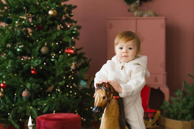Uma criança pequena sentada em um cavalo de madeira perto da árvore de natal