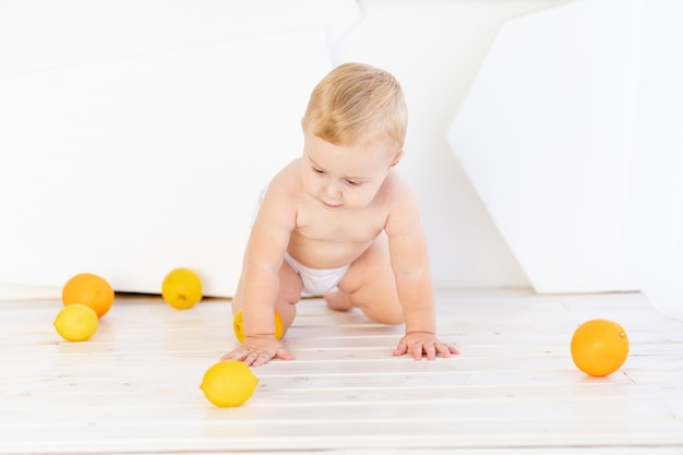 Uma criança pequena, um menino, brinca no chão de uma sala branca e bem iluminada, usando fraldas com limão e laranja