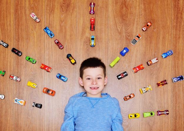 Uma criança pequena, um menino com um suéter azul está sorrindo, deitado no chão de madeira, no contexto de muitos carros de brinquedo.