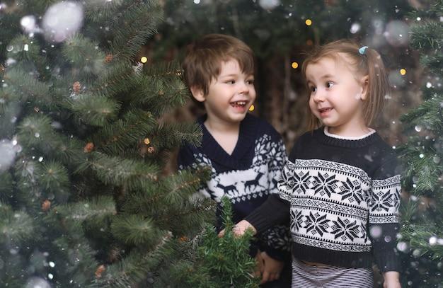 Uma criança perto da árvore do ano novo. as crianças decoram a árvore de natal.