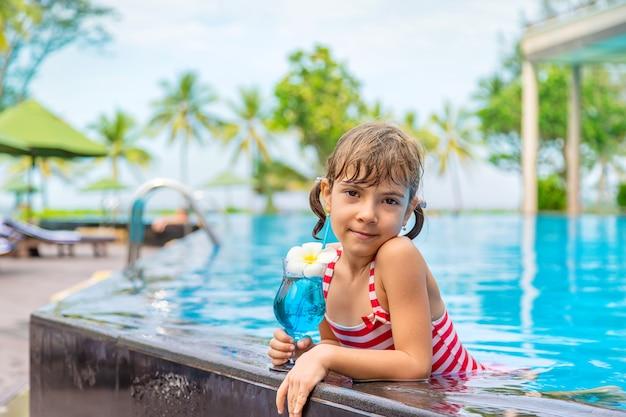 Uma criança perto da piscina bebe um coquetel.