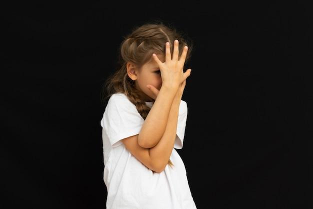 Uma criança posa em um fundo preto.