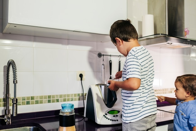 Uma criança preparando panquecas com um robô de cozinha.