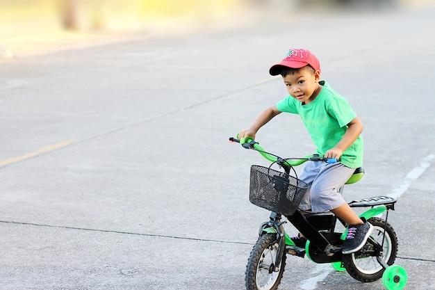 Uma criança que monta uma bicicleta com rodas de treinamento.