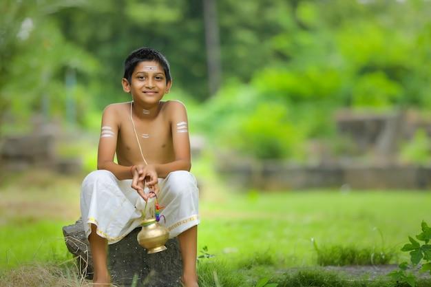 Uma criança sacerdote indiana com pote de água benta