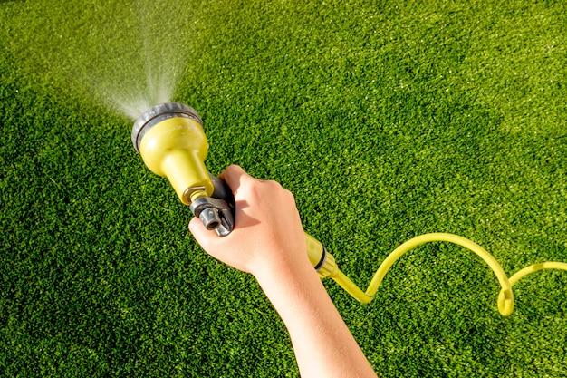 Uma criança se diverte no verão com tarefas domésticas, como regar a grama de seu quintal.