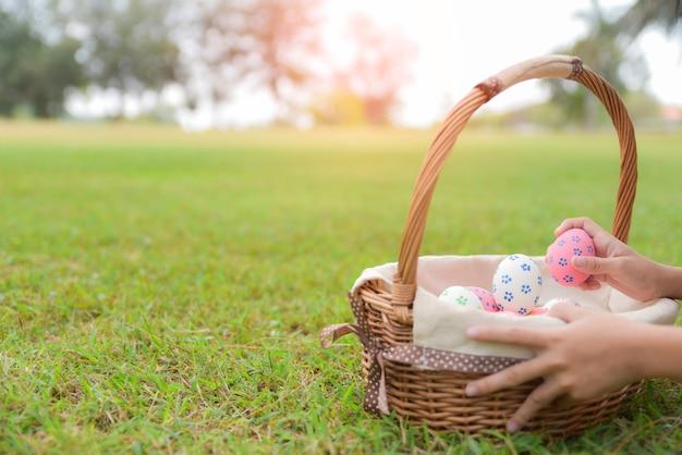 Uma criança se divertindo com os ovos no jardim na grama verde.