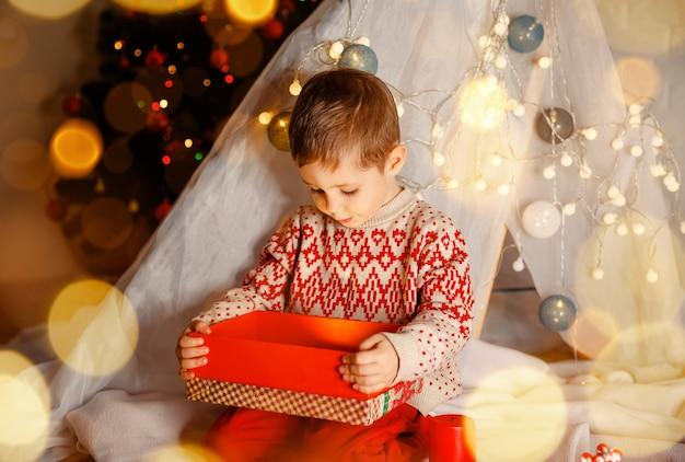 Uma criança se divertindo perto de uma árvore decorada dentro de casa e uma criança fofa surpresa