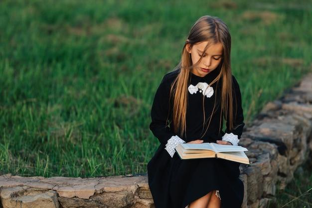 Uma criança se senta em um banco de pedra e lê um livro.