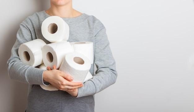Uma criança segura uma braçada de rolos de papel higiênico nas mãos.