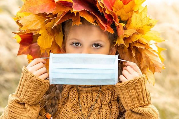 Uma criança segura uma máscara médica contra o coronavírus.