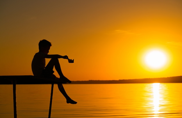 Uma criança senta-se em uma ponte com as pernas para baixo e joga com o navio de papel na mão ao pôr do sol no rio.