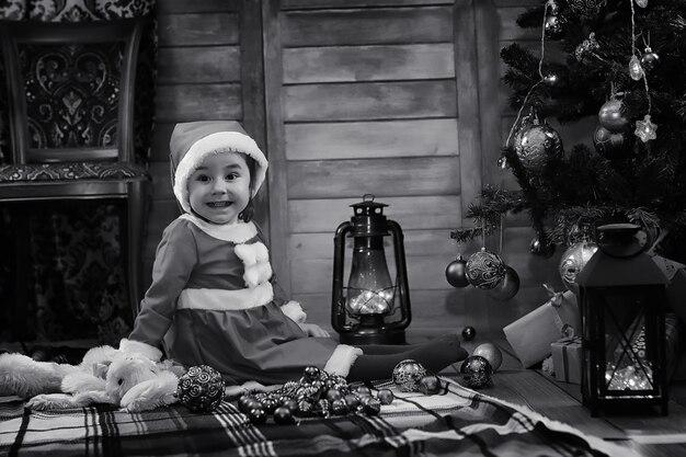 Uma criança sentada em frente a uma árvore de natal esperando o papai noel