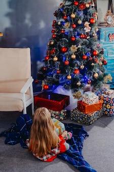 Uma criança sentada no chão olha para uma árvore de natal